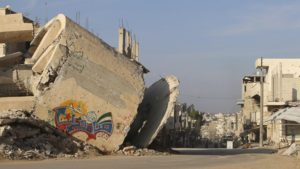The word 'Steadfast' is seen as graffiti on a damaged building in Deraa [Wsam Almokdad/Reuters]