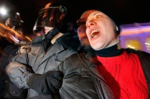 A Russian police officer detain an opposition activist during a protest against vote rigging in St. Petersburg, Russia, on December 4, 2011. (AP Photo/Dmitry Lovetsky)