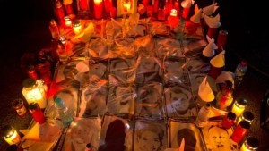 Candles are lit next to photographs of the victims outside the Colectiv nightclub in Bucharest Source: Associated Press
